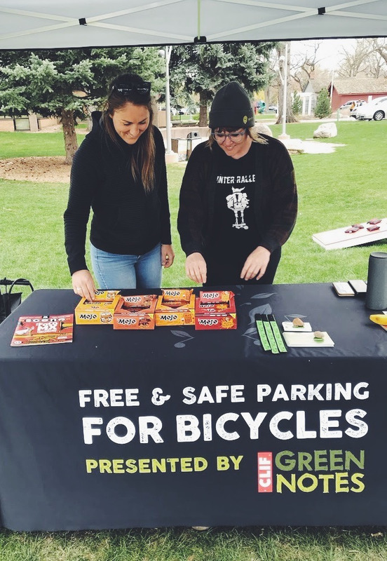 Two bikers grabbing CLIF bars after getting to bike valet